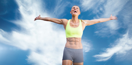 stretched: Fit woman celebrating victory with arms stretched against blue sky with clouds