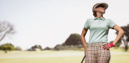 woman golf: Woman playing golf against view of a park Stock Photo