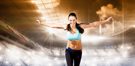 winning pitch: Happy sportswoman is raising arms  against sports arena Stock Photo