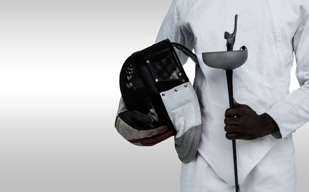 fencing sword: Mid-section of man standing with fencing mask and sword against grey background