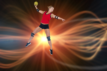 female elbow: Female athlete with elbow pad throwing handball against composite image of orange spotlight
