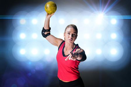 elbow pad: Female athlete with elbow pad throwing handball against spotlights