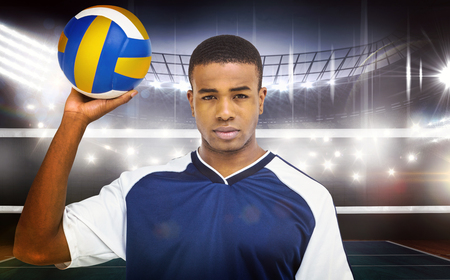 coloured background: Sportsman holding a volleyball against coloured background