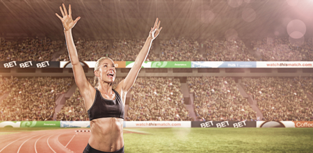 winning pitch: Female athlete posing after victory against view of a stadium Stock Photo
