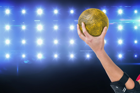 female elbow: Female athlete with elbow pad holding handball against composite image of blue spotlight Stock Photo
