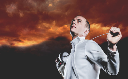 swordsman: Swordsman holding fencing sword against gloomy sky