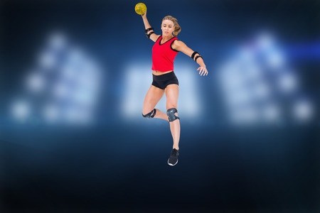 elbow pad: Female athlete with elbow pad throwing handball against composite image of spotlight Stock Photo