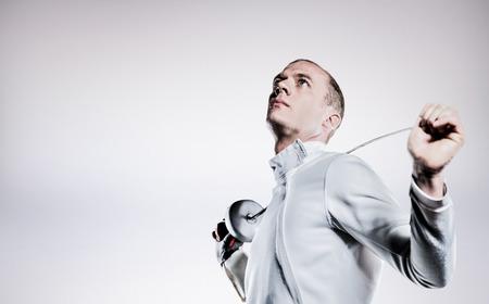 swordsman: Swordsman holding fencing sword against grey background
