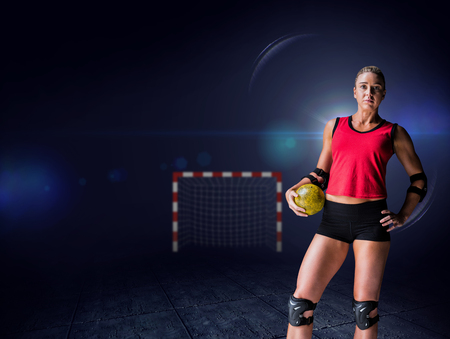 elbow pad: Female athlete with elbow pad holding handball against view of lighting