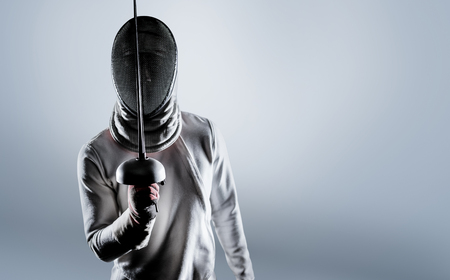 Man wearing fencing suit practicing with sword against grey vignette Imagens - 58430878