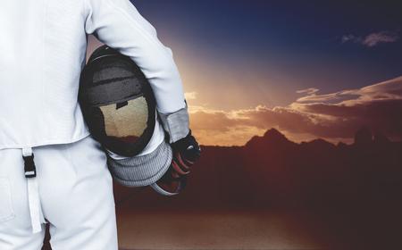 swordsman: Rear view of swordsman holding fencing mask and sword against composite image of landscape