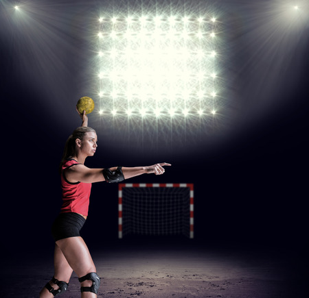 elbow pad: Female athlete with elbow pad throwing handball against view of spotlights