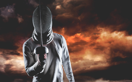 fencing sword: Man wearing fencing suit practicing with sword against aerial view of a city on a cloudy day