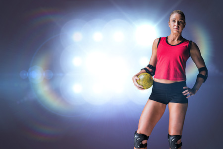 elbow pad: Female athlete with elbow pad holding handball against spotlights Stock Photo