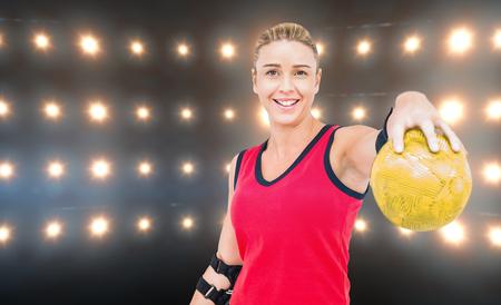 female elbow: Female athlete with elbow pad holding handball against composite image of orange spotlight Stock Photo