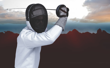 composite image: Man wearing fencing suit practicing with sword against composite image of landscape