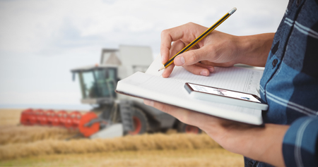 Farmer with pencil on book against view of a harvester