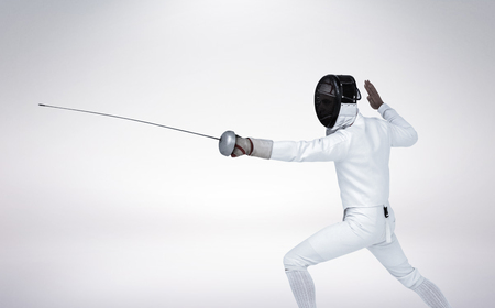 sabre's: Man wearing fencing suit practicing with sword against grey vignette