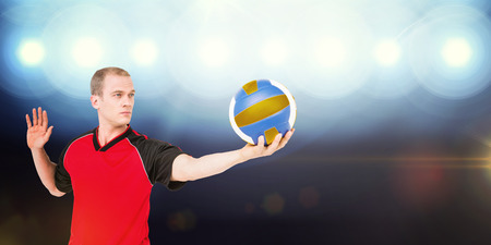pelota de voley: Sportsman getting ready to serve while playing volley ball against view of spotlights