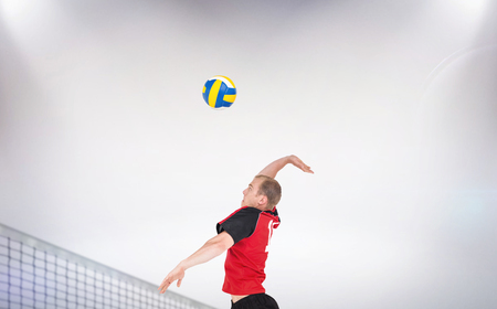 hitting: Composite image of sportsman hitting volleyball against a grey background