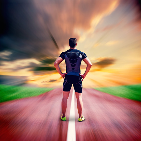 skintight: Composite image of athlete man posing with hands on hips against blurred background Stock Photo