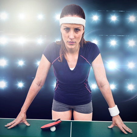 digitally generated image: Angry female athlete leaning on hard table against digitally generated image of blue spotlight