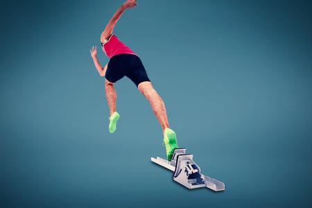 starting blocks: Composite image of male athlete running from starting blocks against blue background