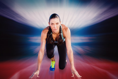 starting block: Composite image of sporty woman in the starting block against a design background Stock Photo