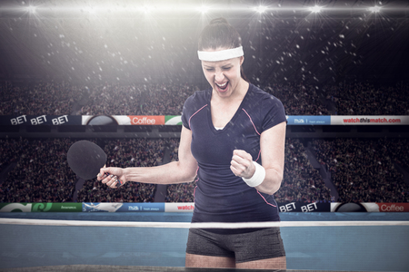 winning pitch: Composite image of female table tennis player posing after victory in a stadium Stock Photo