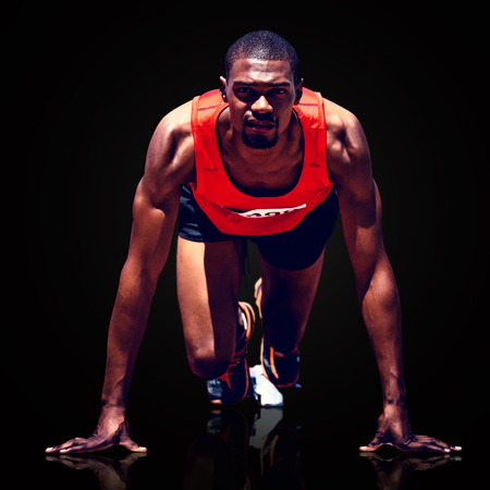 starting block: Composite image of athlete man in the starting block against black background Stock Photo