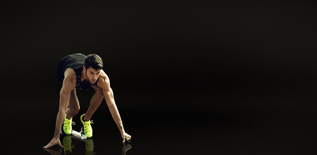 starting block: Composite image of sportsman waiting on the starting block against a black background
