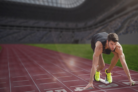 starting block: Composite image of sportsman waiting on the starting block in a stadium Stock Photo