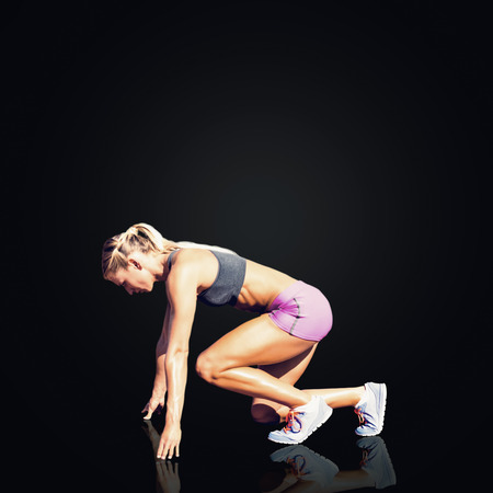 starting position: Composite image of sportswoman in starting position against black background