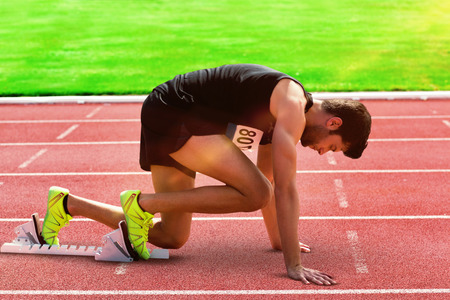 starting line: Composite image of sportsman waiting on the starting line on athletics field Stock Photo