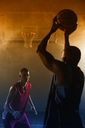 trato amable: Retrato de dos hombres jugando al baloncesto en un gimnasio