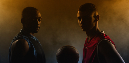 Two basketball player looking the camera with a basketball between them