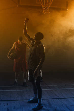 rival: Victorious basketball player raising his arms up while his rival looking down
