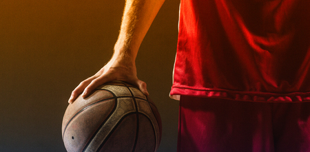 held: Close up on a basketball held by basketball player on a gym