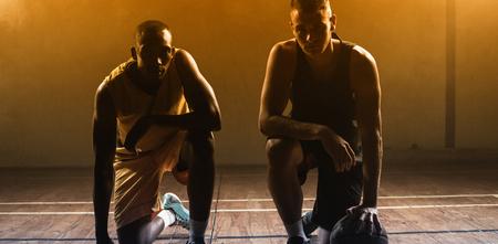 trato amable: Retrato jugadores de baloncesto que presenta en sus rodillas en un gimnasio Foto de archivo