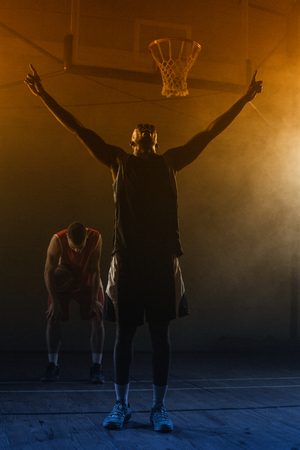 the victorious: Victorious basketball player raising his arms up while his rival looking down