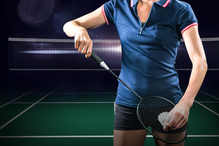 racket stadium: Badminton player holding a racket ready to serve against view of a badminton field