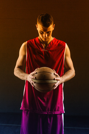 eyes looking down: Portrait of basketball player holding a ball on a gym