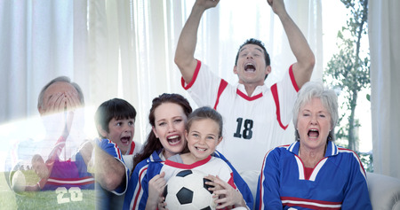 football teams: Composite image of family watching a football match in television at home