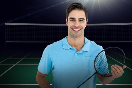 racket: Composite image of badminton player holding badminton racket against badminton field