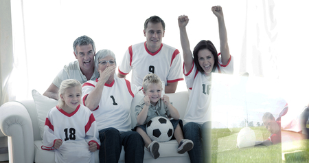 Composite image of happy family watching a football match in television at home photo