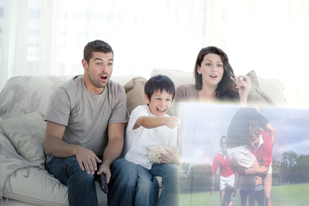 family sofa: Composite image of happy family watching television on the sofa