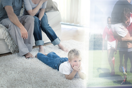 sports programme: Composite image of cute boy lying on carpet is watching sport on television in front of his parents at home Stock Photo