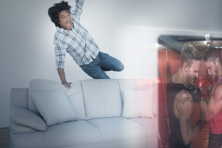boxing match: Composite image of excited man are watching boxing match on television at home Stock Photo