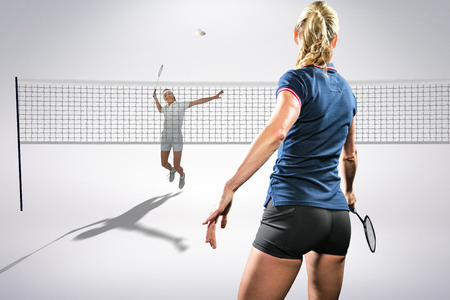 badminton racket: Composite image of badminton players playing badminton against white background
