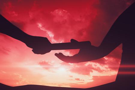 Man het stokje doorgeven aan partner op het goede spoor tegen hemel en bergen Man het stokje doorgeven aan partner op het goede spoor in de sportschool Stockfoto